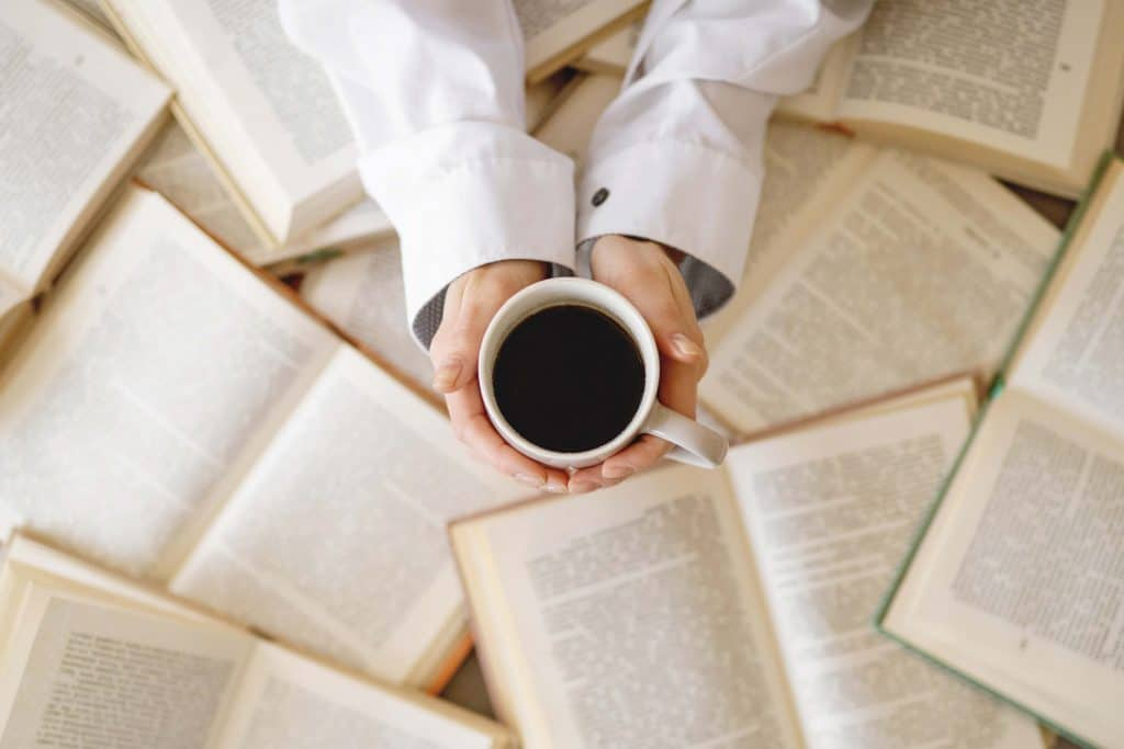 hands holding a black coffee over open books